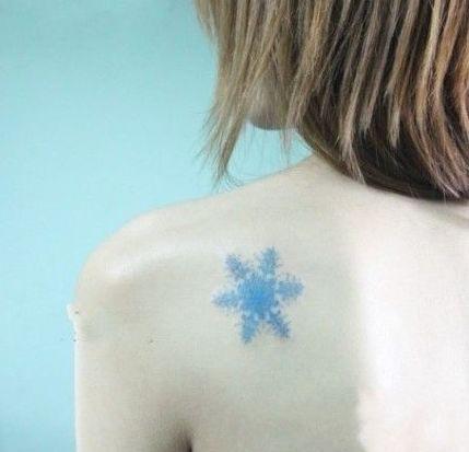 女生肩背精美的彩色雪花纹身图案