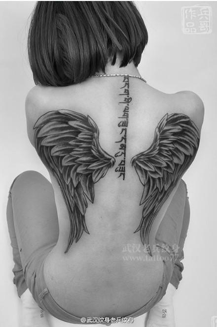 时尚的美女满背翅膀纹身;