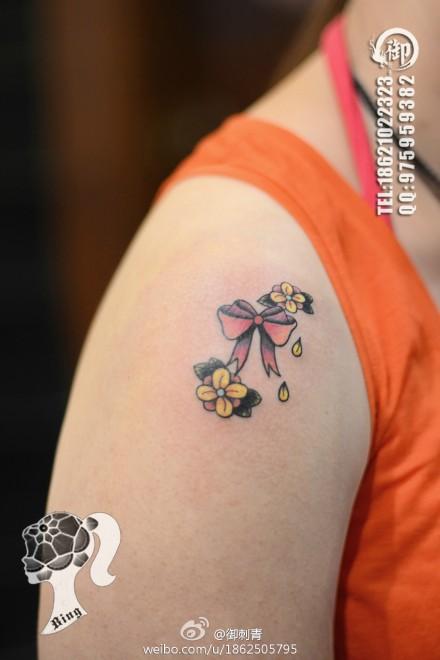 女生手臂小巧经典的蝴蝶结与花卉纹身图案图片