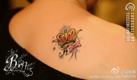 女生肩膀处小巧潮流的皇冠蝴蝶结纹身图案